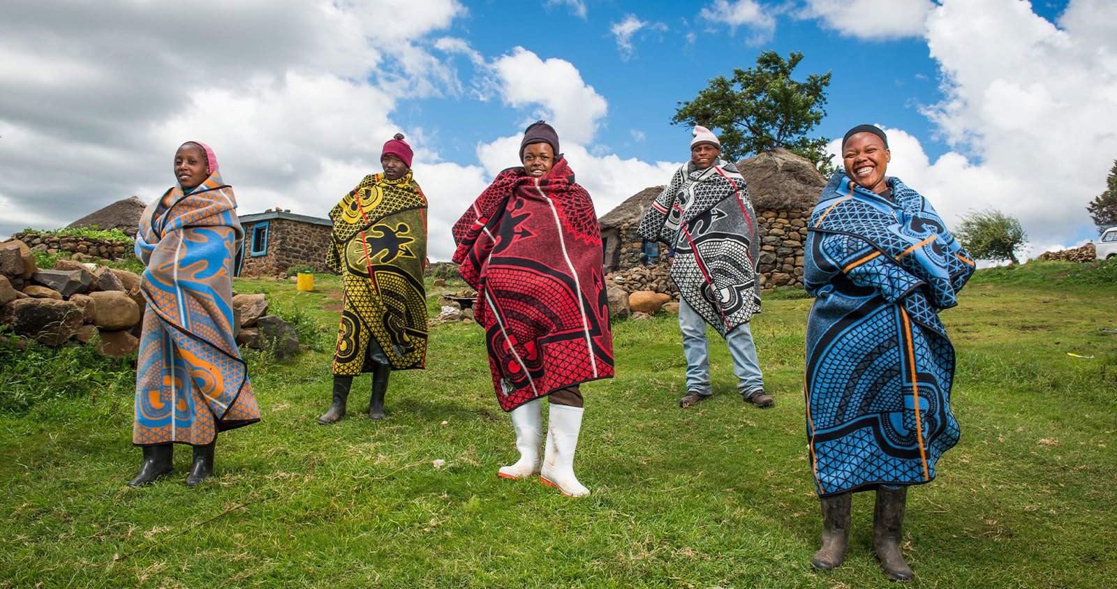 African blanket the basotho blanket worn by basotho people standing on green grass in front of traditional housing