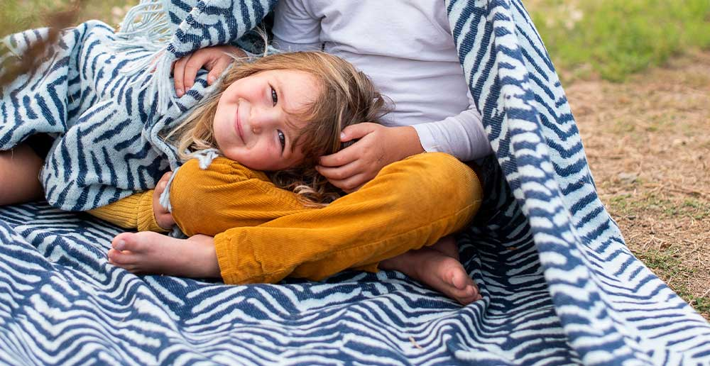 Kids lying on african blanket with blue brushstrokes