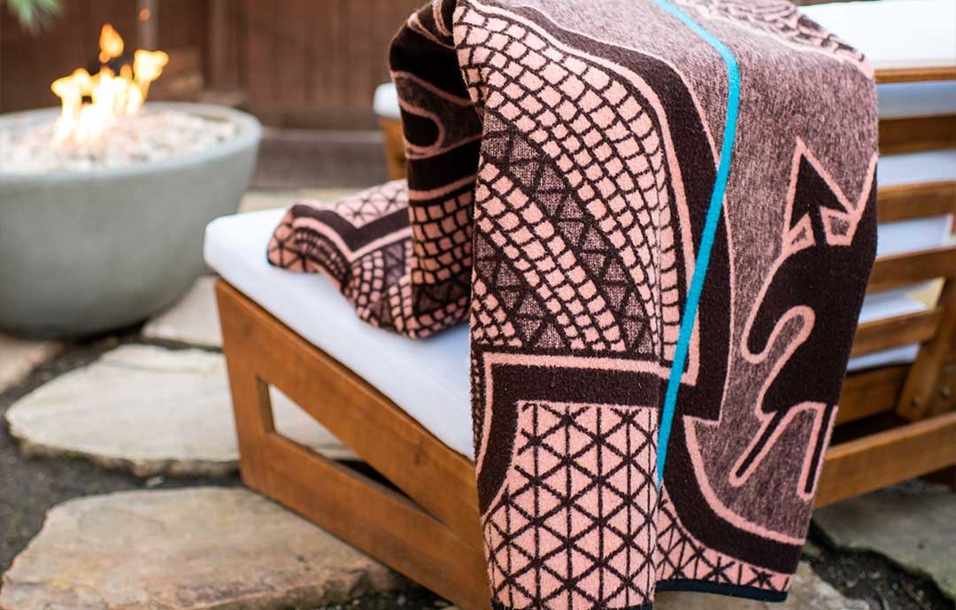 Basotho heritage wool blanket wrapped over the back of a chair in front of a fire