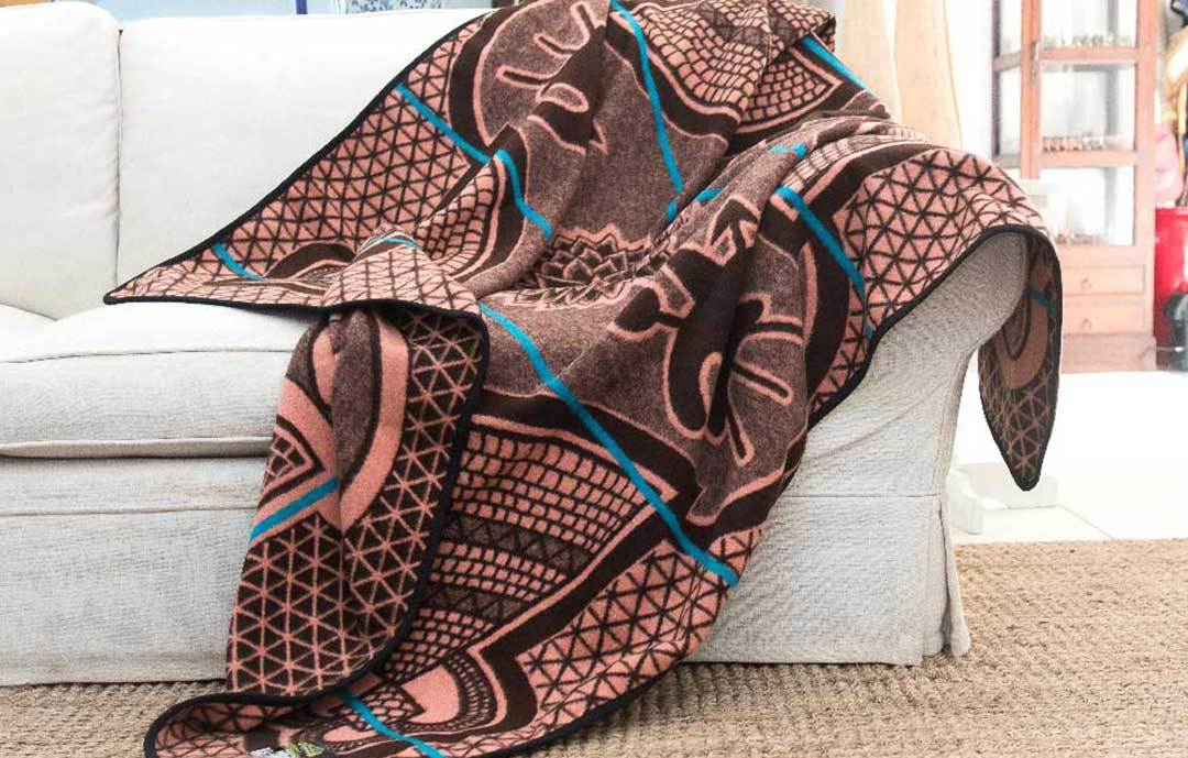 A Basotho heritage wool blanket from Africa draped over a white couch