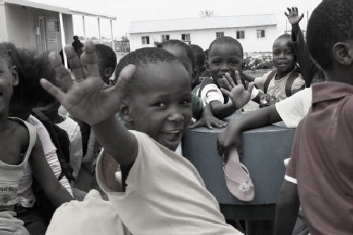 african kids on a playpump that creates water from play