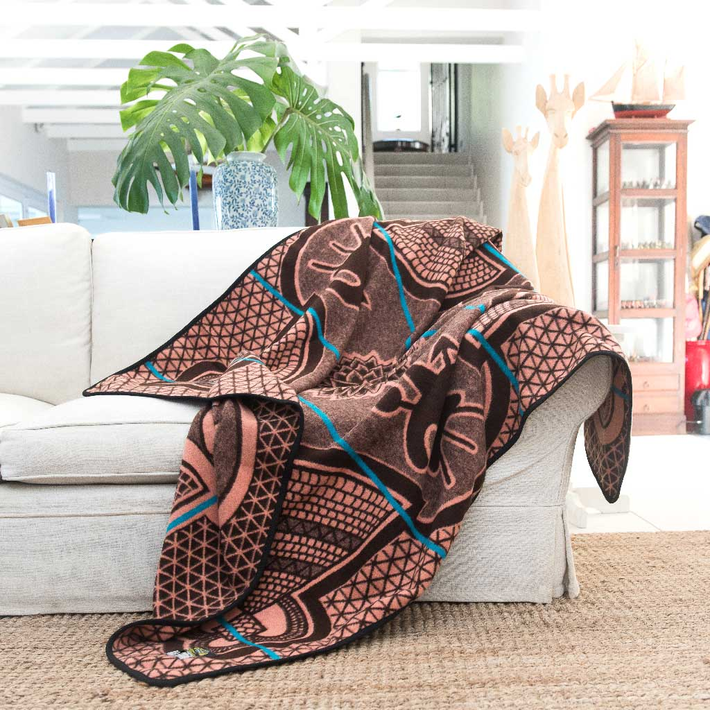 Basotho Heritage Kharetsa blanket and wrap or throw handcrafted in South Africa chromatic Salmon and peacock throw drapped across a sofa in a beautiful modern house