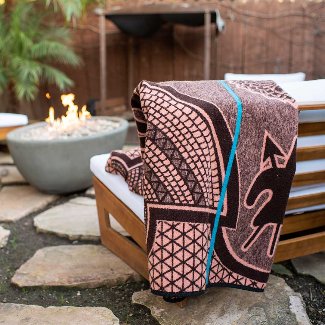 Basotho Heritage blanket and wrap or throw handcrafted in South Africa chromatic Salmon and peacock throw drapped across a sofa in a beautiful modern house