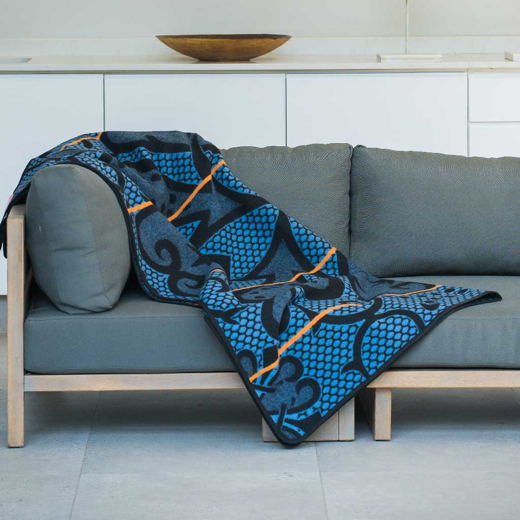 Authentic SeannaMarena Basotho Heritage Wool Blanket and wrap or throw sustainably and ethically crafted in South Africa draped over modern house in South Africa