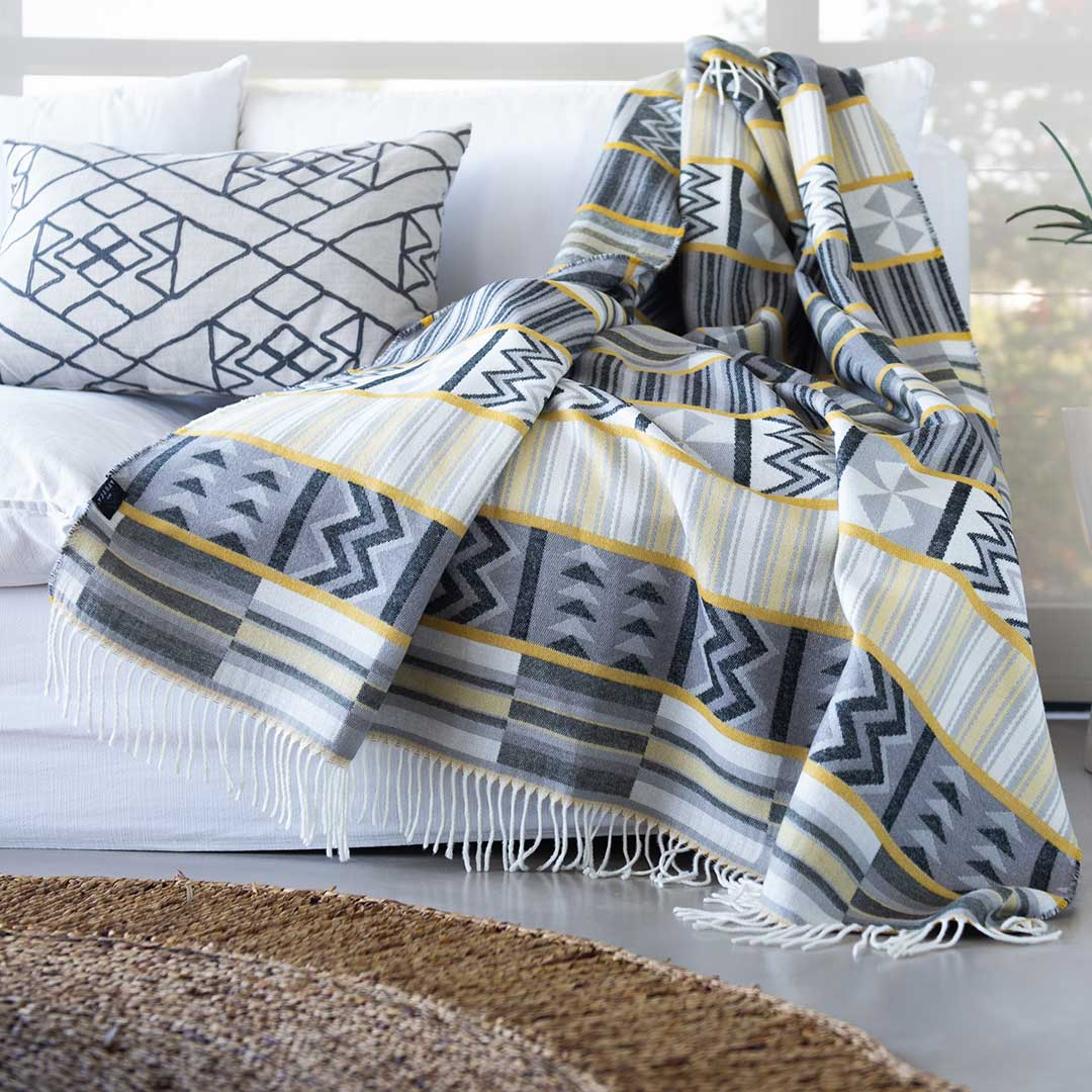 This beautiful and vibrant throw Ghana kente Throw Sustainably and ethically crafted in South Africa, the My Africa collection is a range of incredibly soft, warm, and exceptionally durable blankets that take their inspiration from the cultures and people that inhabit this beautiful land. This Image is of a Kente throw draped over a modern couch in an African House
