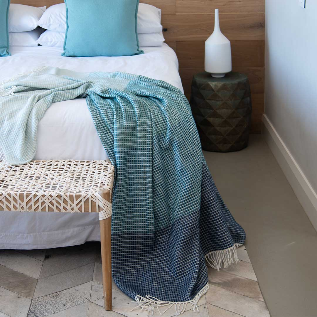 Lyric collection wrap, blanket or throw sustainably and ethically made in South Africa drapped over a bed in a modern house in South African home
