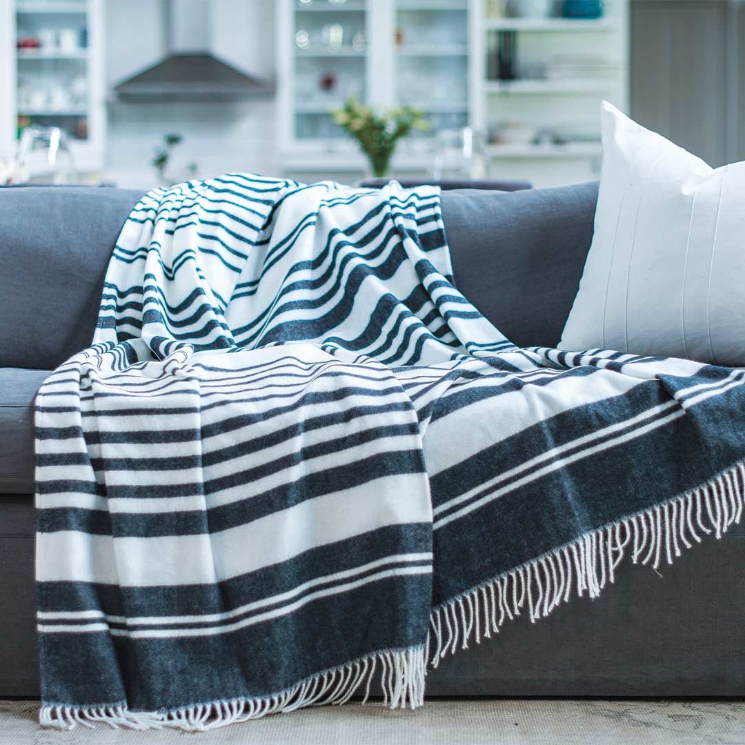 Xhosa Nation wrap, blanket or throw sustainably and ethically made in South Africa. This xhosa inspired Black and white stripe is draped over a grey couch in a modern home