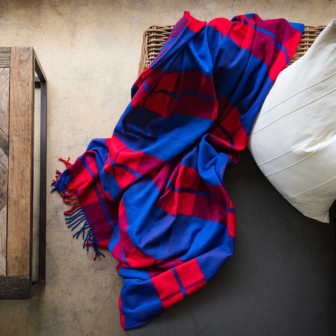 Maasai Shuka incredibly soft, warm, and exceptionally durable blankets throw in plaid red and royal blue Sustainably and ethically crafted in South Africa lying on a modern styled wicka chair in modern house