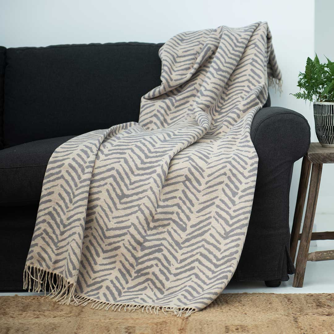 Brush strokes wrap, blanket or throw sustainably and ethically made in South Africa drapped over a modern House in South African home