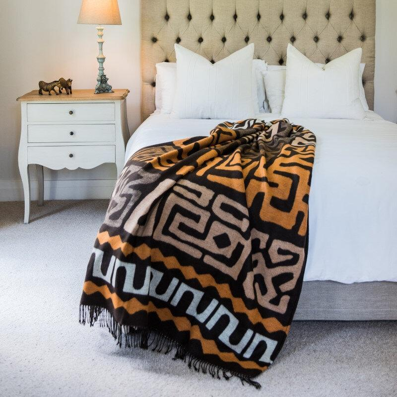 congolese kuba cloth wrap, blanket or throw handcrafted in South Africa in coffee and clay colors lying draped over a modern looking bed