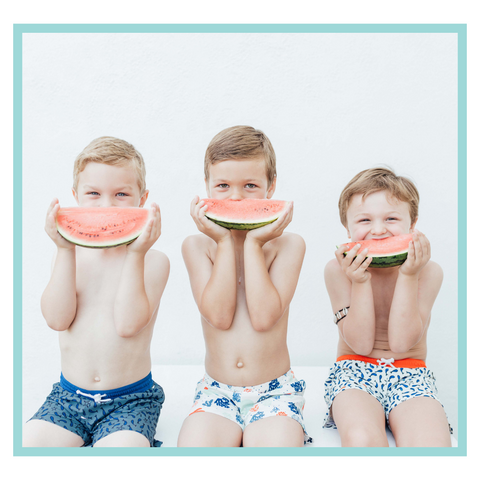 Boys in Folpetto swim shorts eating watermelon to keep hydrated in the sunshine