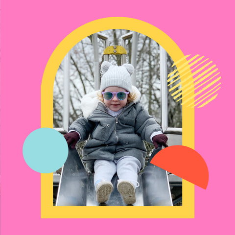 Little girl on slide wearing her sunglasses and winter hat in the sunshine