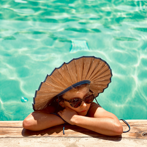 Girl in pool wearing sunglasses and Lorna Murray hat