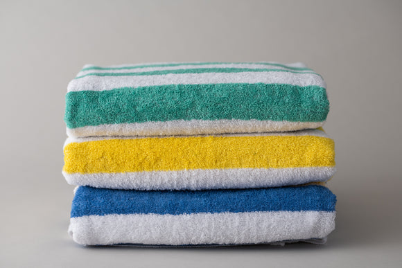 Green, Yellow and Blue Island stripe pool towels folded and stacked. Thomaston Mills Towels.