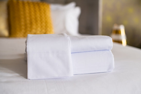 Thomaston T-250 Royal Suite pillowcase laid over folded sheets laying on a bed made with Thomaston T-250 Royal Suite sheets and pillowcases.