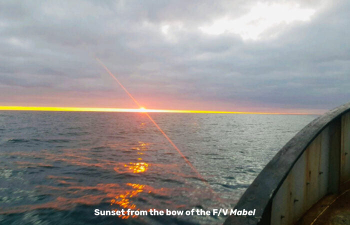 A sunset viewed from the bow of a fishing vessel