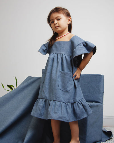 Girl Denim dress with ruffle edged hem and ruffle shoulders details.