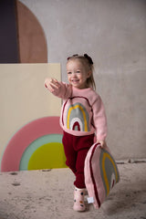 Baby girl is wearing organic cotton knitted sweater with rainbow motif