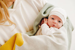 Baby is wrapped in organic knitted blanket from Nordic Lemon