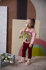 Little baby girl is playing around in knitted organic cotton sweater