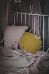 Nordic lemon cushion shaped as a lemon and soft toy elephant on the bed