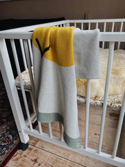 Nordic lemon organic cotton blanket with sun motif.
