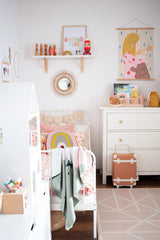White walls for kids room with knitted accents on the bed