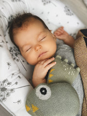 Baby girl is sleeping with knitted organic toy Hipo