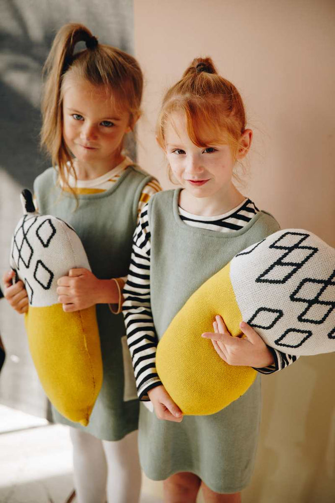 Girl models wearing Nordic Lemon pistachio dresses, holding acorn cushion in harvest mustard