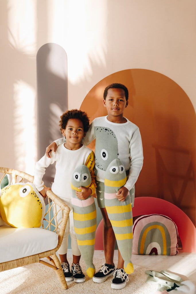Boys models wearing Nordic Lemon organic clothing sweaters with knitted sprat cushion.