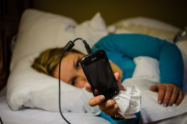 Person Holding Phone In Bed