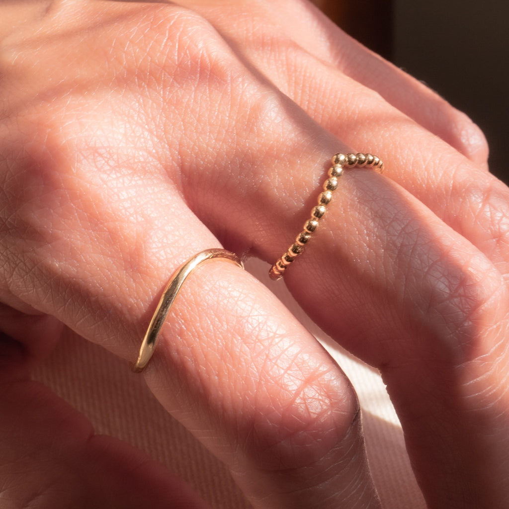 Hand wearing two rings in picture.  Ring on the right is Beaded V shaped yellow gold ring.  The ring on the left is a curved thin yellow gold ring.