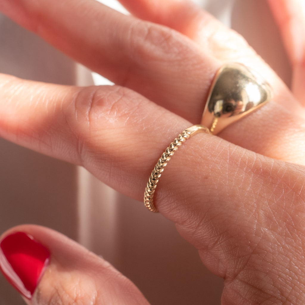 Up close image of model wearing yellow gold braided band.  Ring is paired with a yellow gold dome ring.