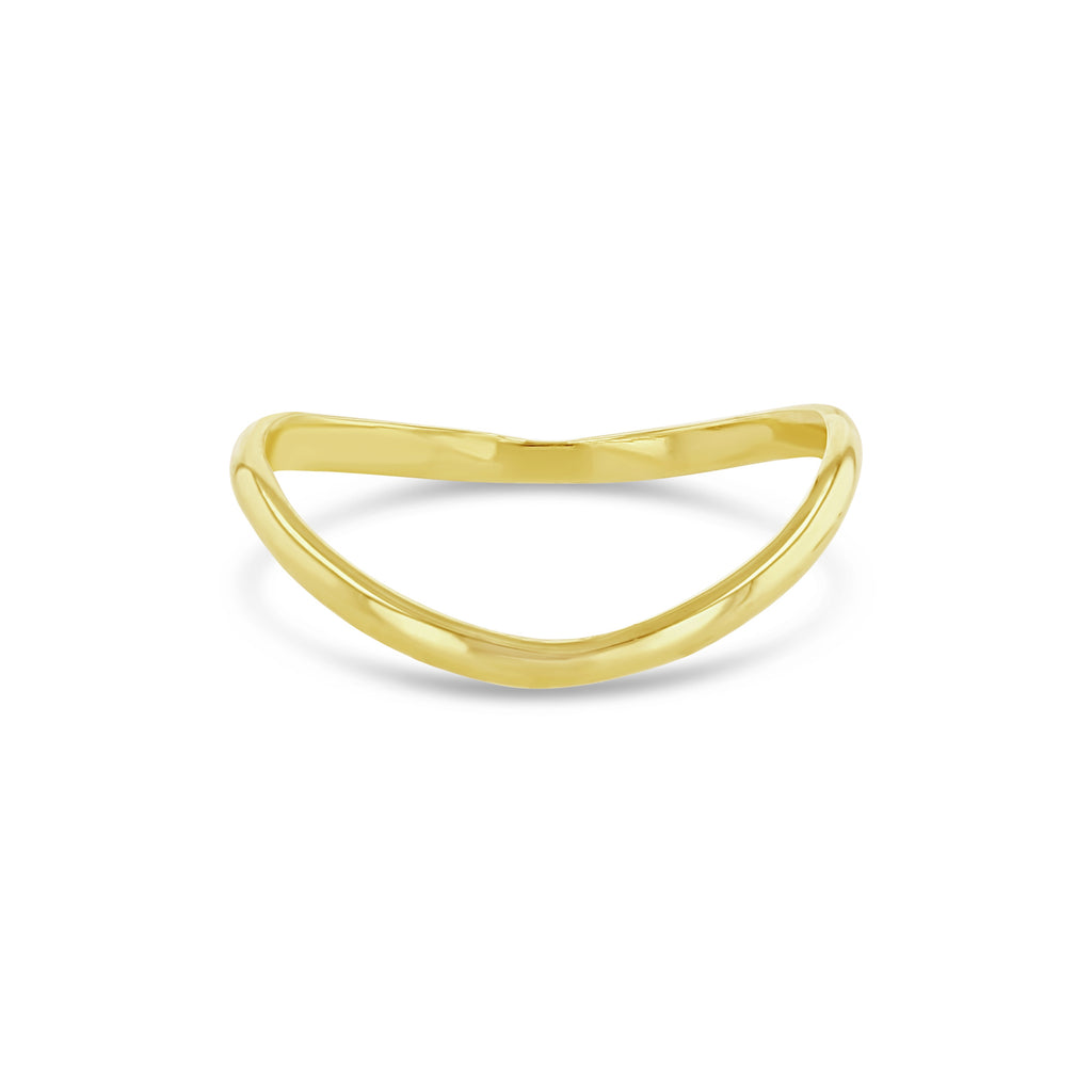 Curved thin yellow gold ring sitting up against white background.