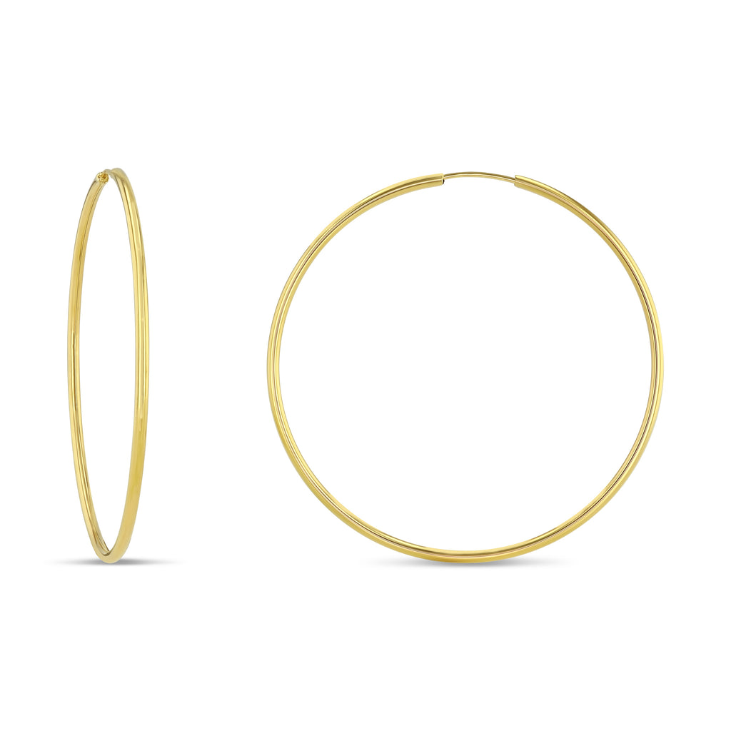Thin yellow gold hoops.  Left earring is on its profile to show the delicate hoops. Large hoops against white background.