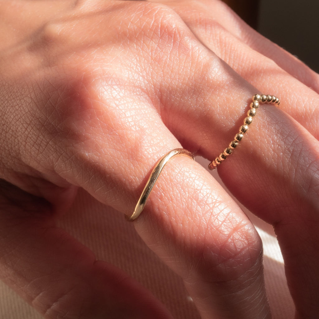 Model wearing yellow gold curved thin ring forming a U-shape on her finger.  Model is also wearing yellow gold beaded V ring.