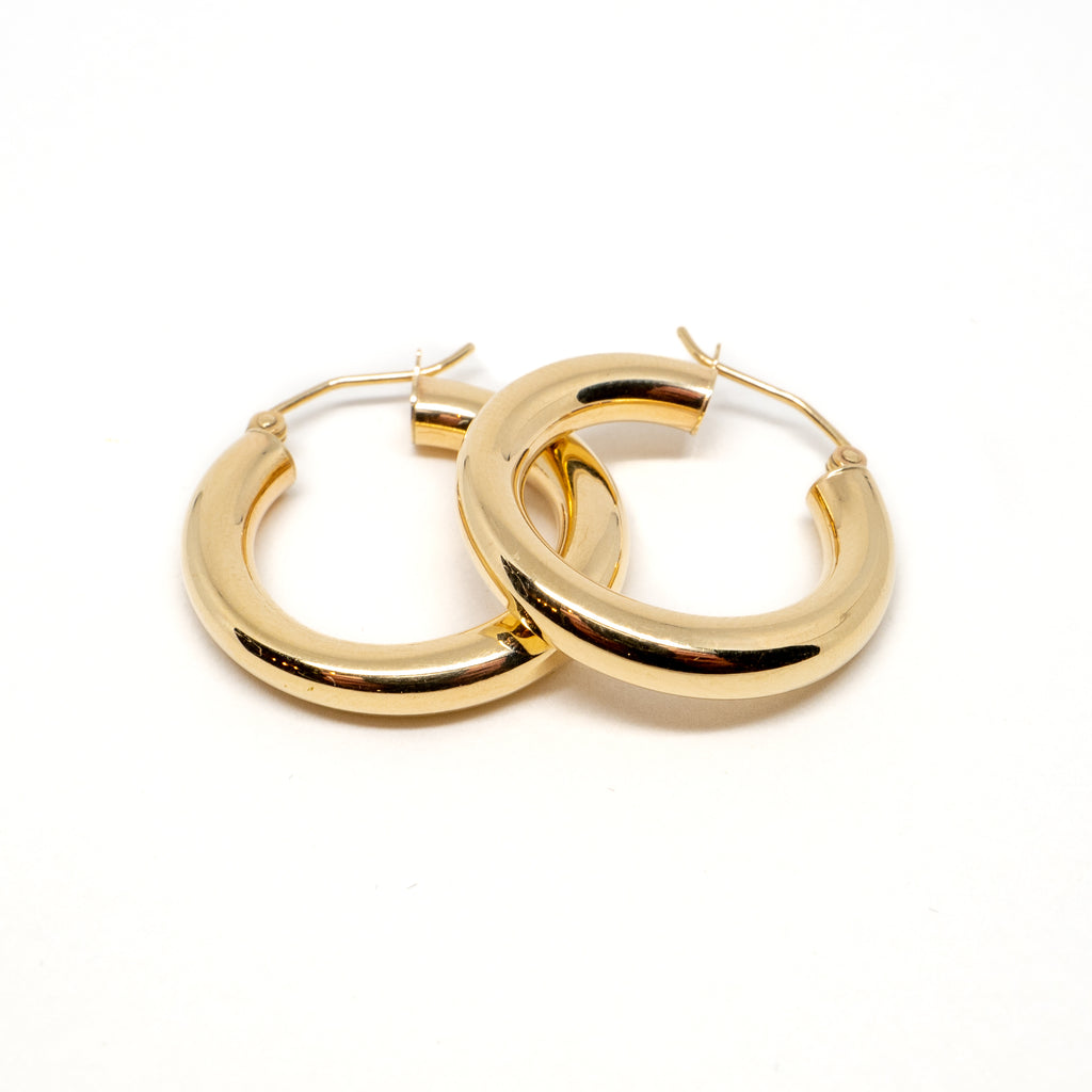 Yellow gold thick earrings laid upon each other.