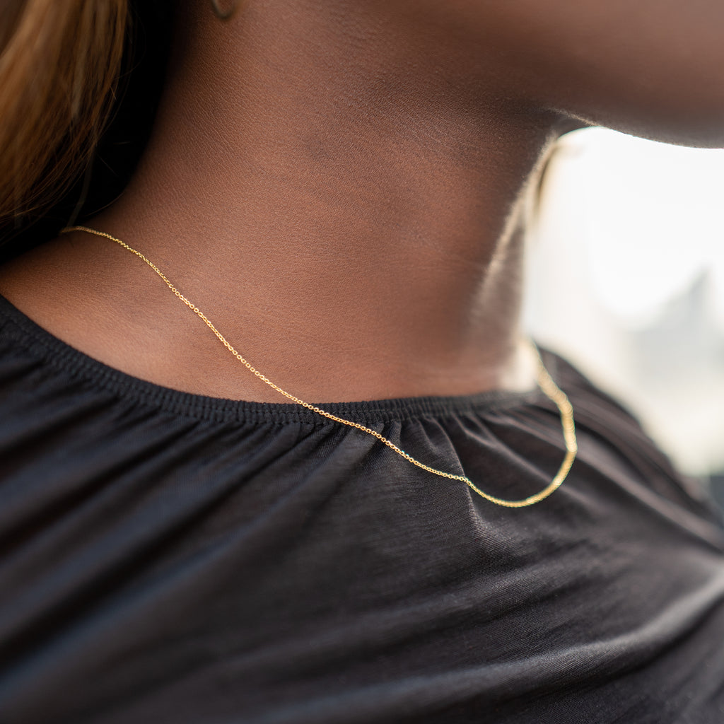 Model wearing stackable chain.  Yellow gold necklace against black top.