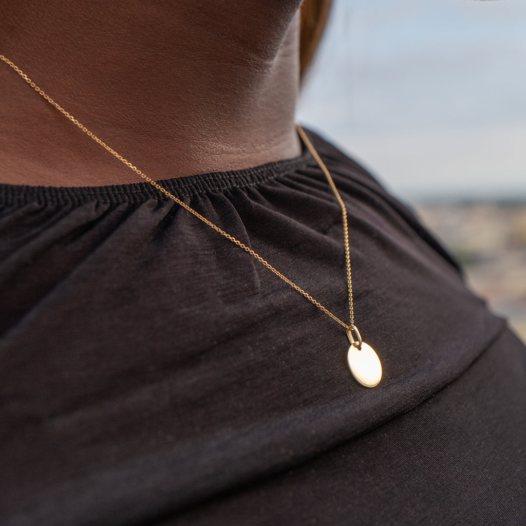 Model wearing Moneda necklace.  Measures 18 inches and sits perfectly under collarbone.  Necklace is 100% yellow solid gold.  Delicate and vibrant enough to add the perfect amount of sparkle to any outfit.