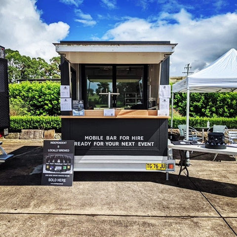 Image of set up bar on trailer with open awning and beer taps