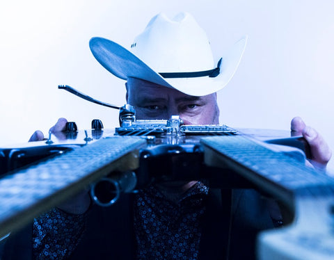 Man in cowboy hat looking down the neck of guitar