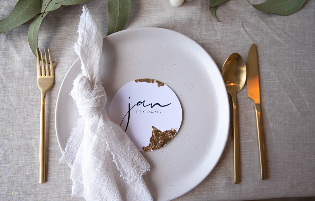 milk white frayed cotton napkins with beige linen tablecloth & gold cutlery