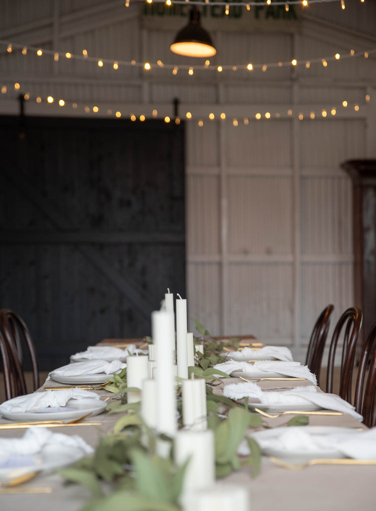 wedding table setting with milk white frayed cotton napkins, beige linen tablecloth, gold cutlery, gum foliage