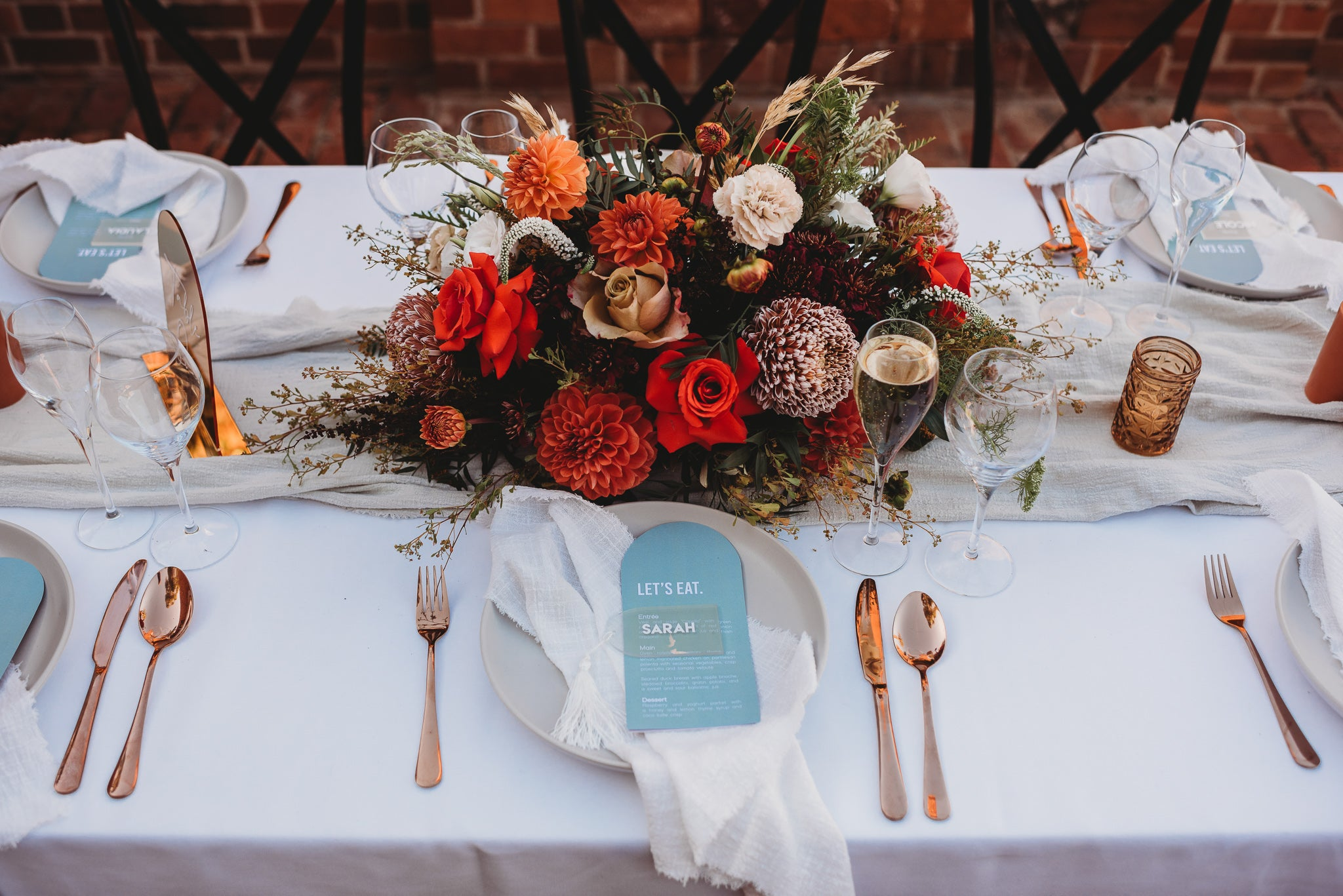 wedding reception with white napkins and red romantic florals