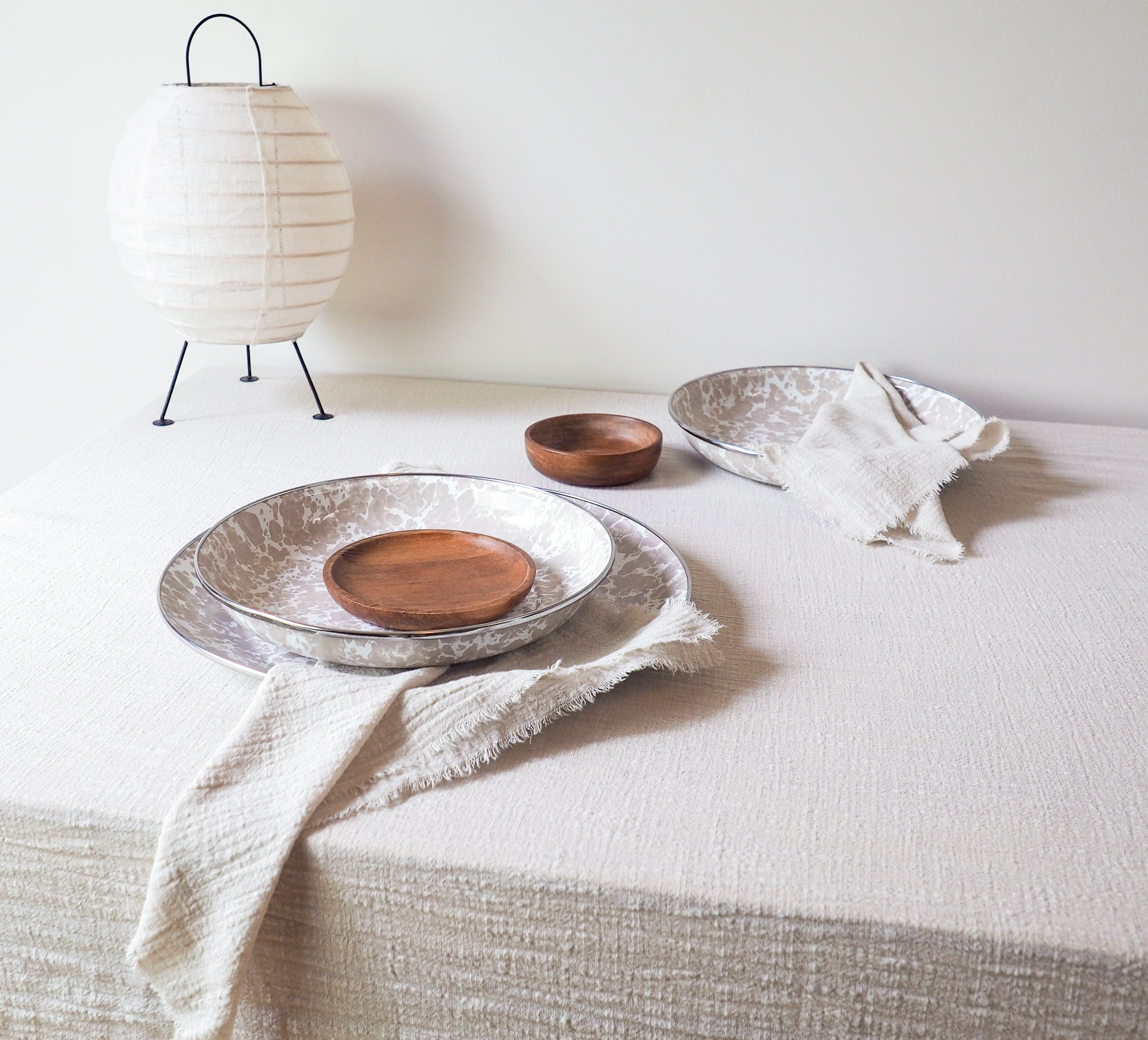 enamel wooden plate and bowl styled with table linen sand cotton napkins and sand cotton table runner