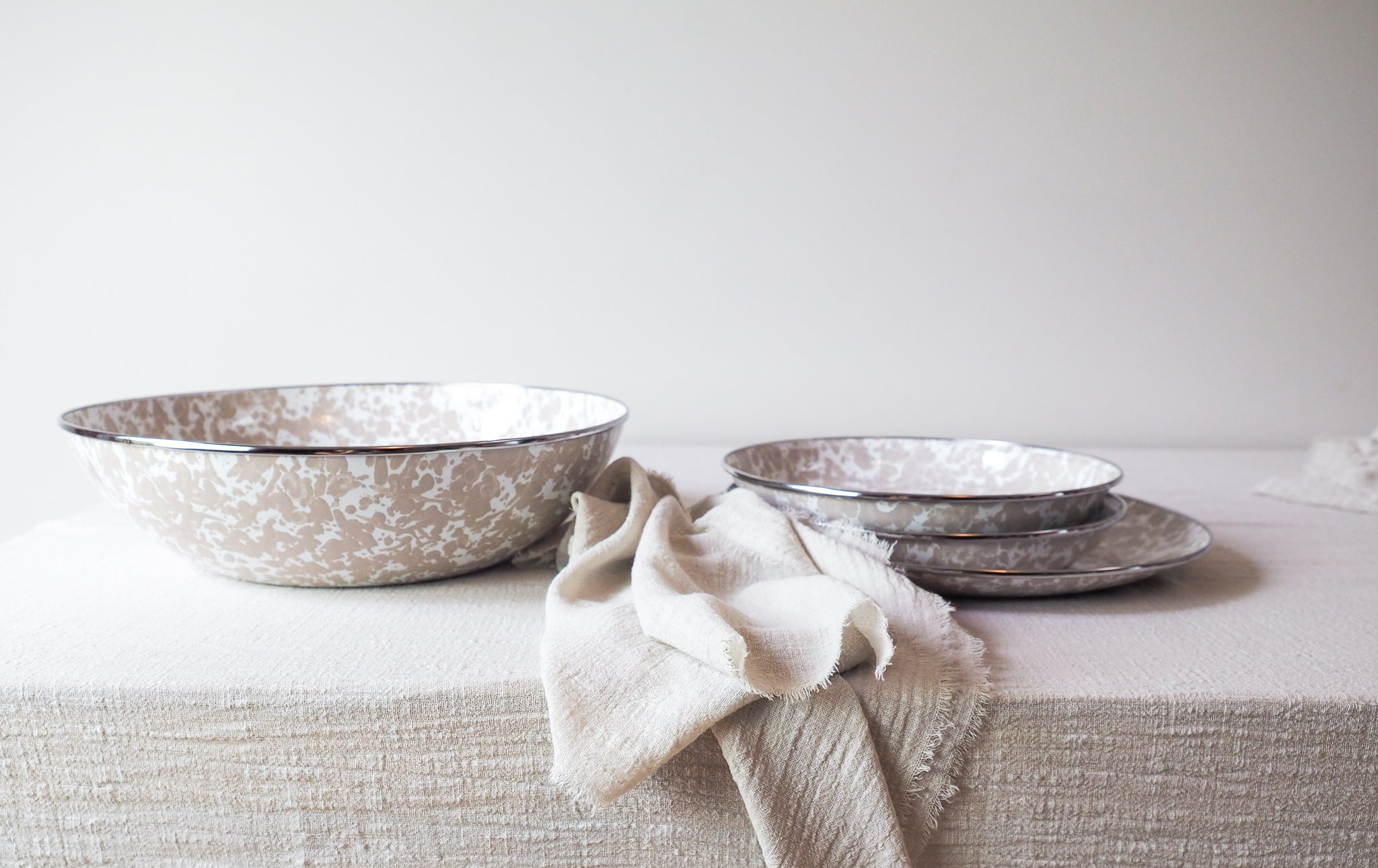 enamel plate and bowl styled with table linen sand cotton napkins and sand cotton table runner