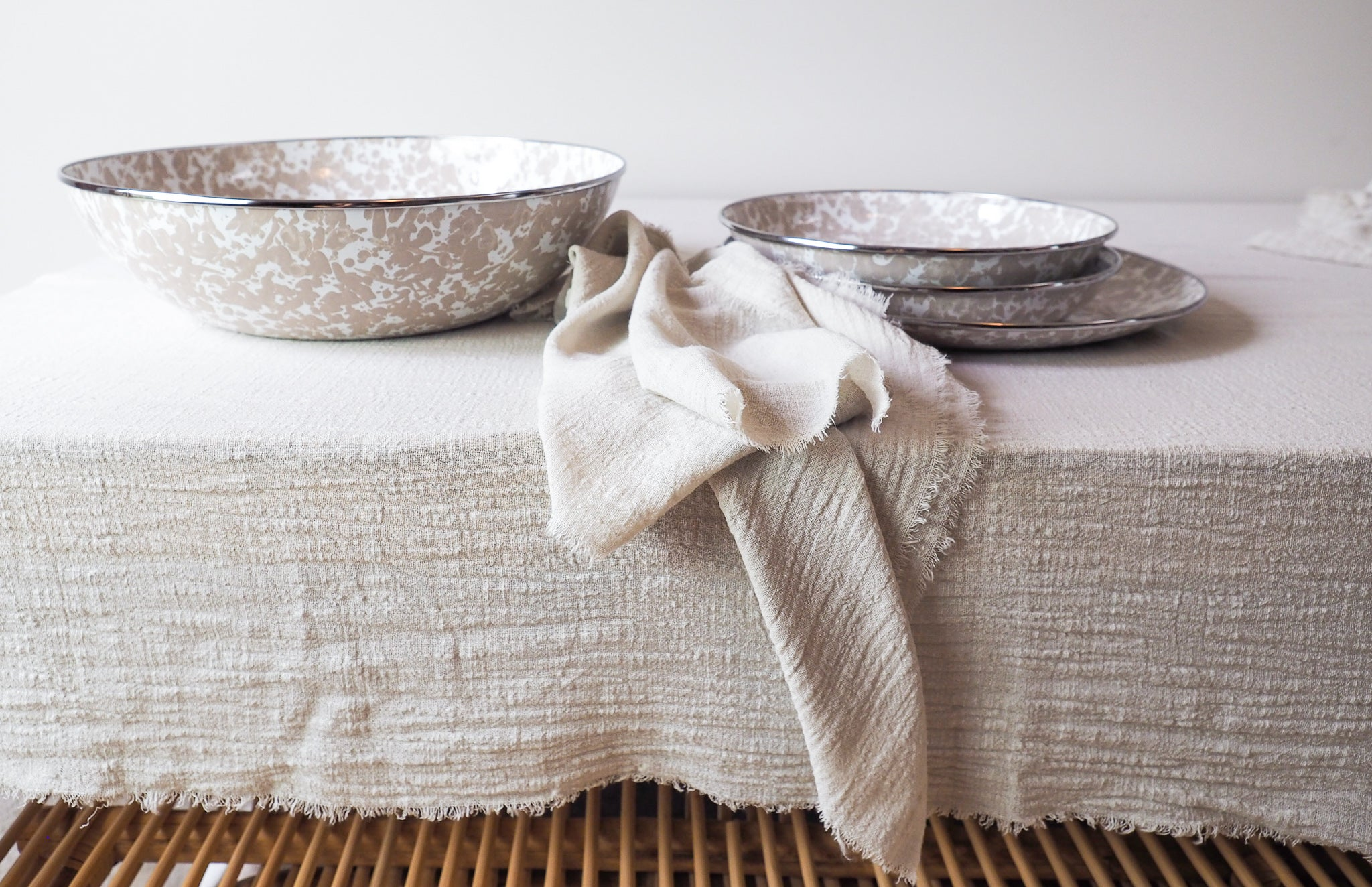 enamel bowl and plate on sand cotton napkins and sand cotton table runner