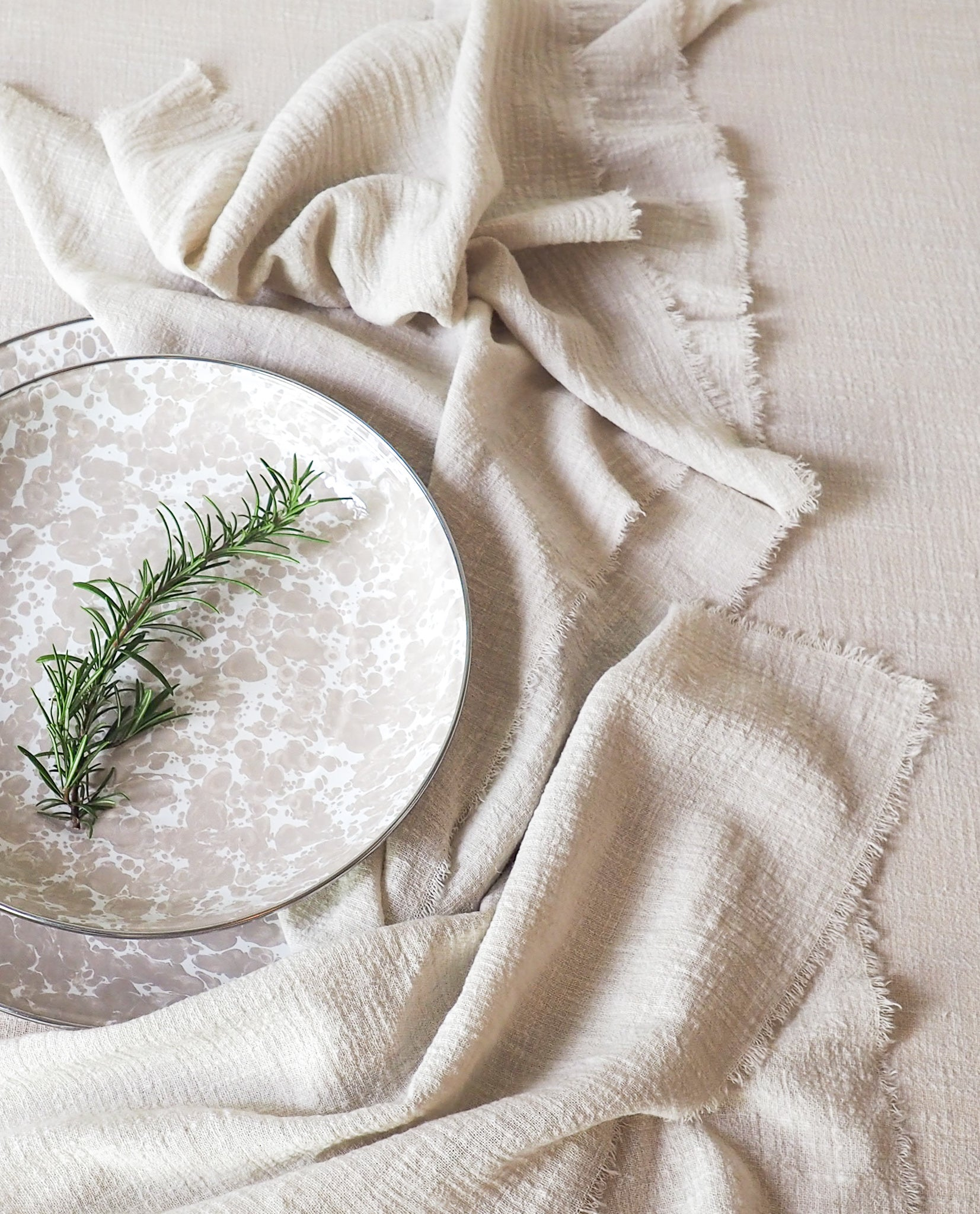 enamel plate styled with table linen sand cotton napkins and sand cotton table runner