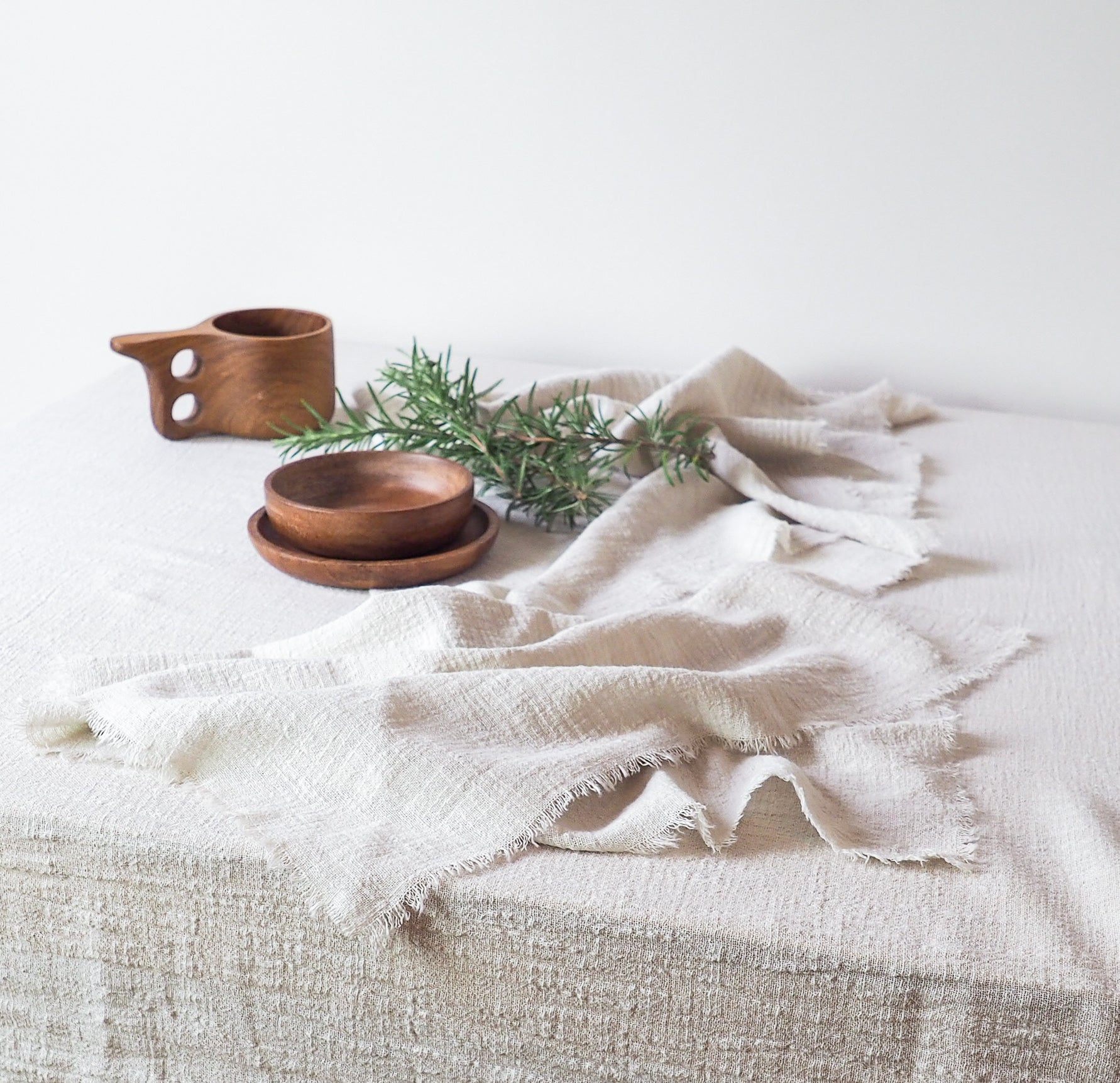 wooden cup and bowl on sand cotton napkins and sand cotton table runner