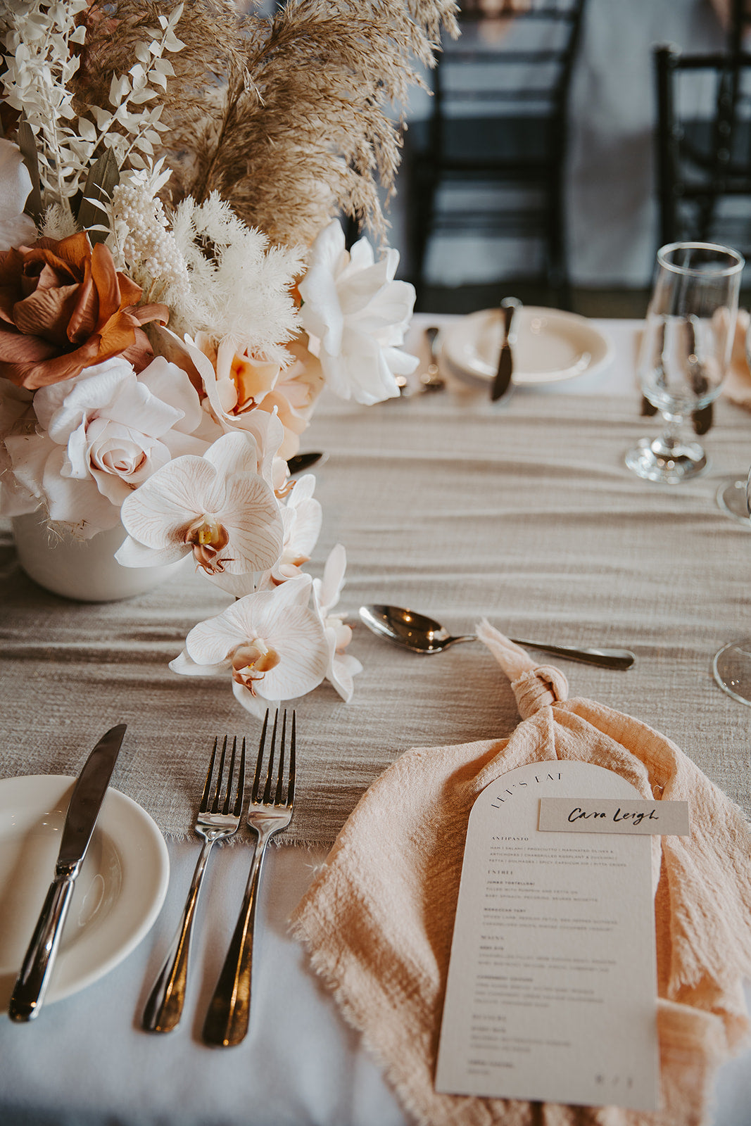 peachy romantic boho summer wedding reception with blush pink napkins and light grey table runners